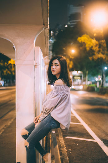 Portrait of beautiful young woman on road at night