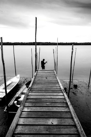 Rear view of man fishing in lake by pier against sky
