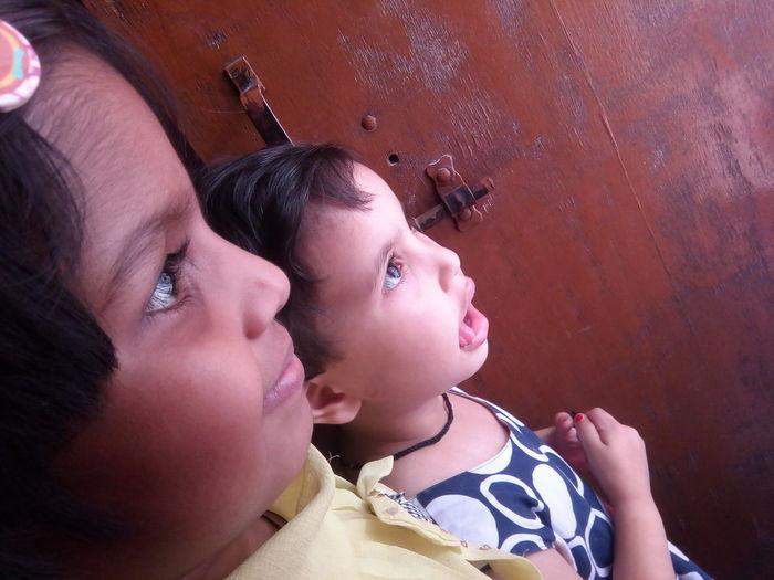 Side view of siblings looking away at home