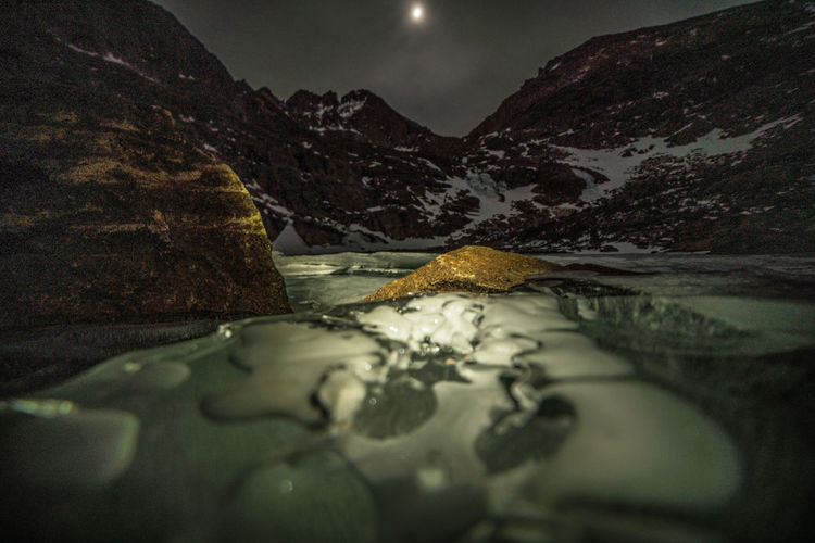 Close-Up Of River Against Mountains At Night