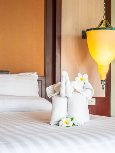 Flowers And Towels On Bed At Hotel Room