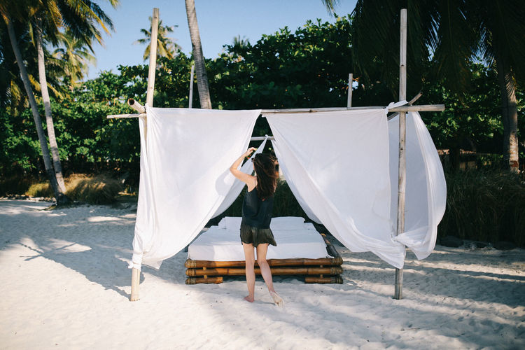 Tree One Person Plant Full Length Real People Leisure Activity Lifestyles Tent Textile Outdoors Front View Women Resort Summer Woman Sunlight Day Sunbed Luxury Beach Sheets Curtain White Minimal Lifestyle