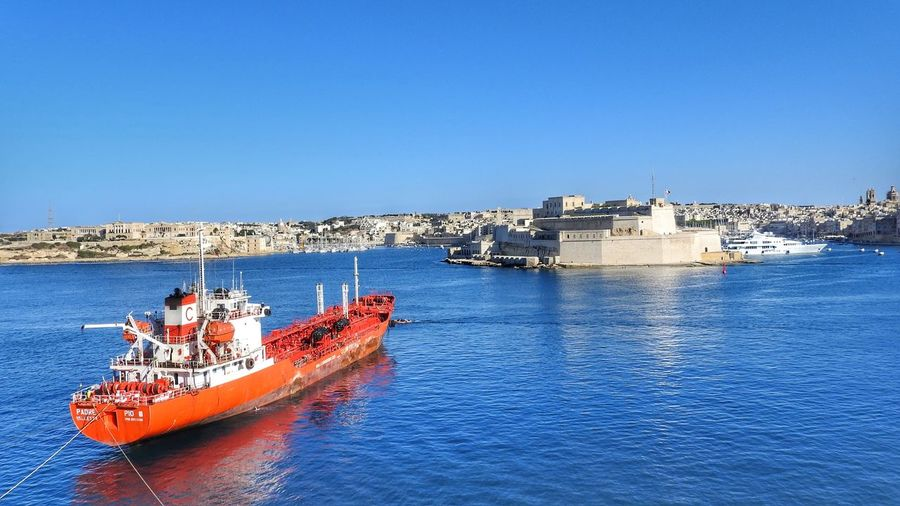 View at Grand Harbour with red vessel in Valetta, Malta Architecture Blue Sea Building Exterior Castle Cityscape Clear Sky Day Grand Harbour Harbor Harbour Harbour View Malta Nautical Vessel No People Outdoors Red Red Boat Sea Sky Transportation Water