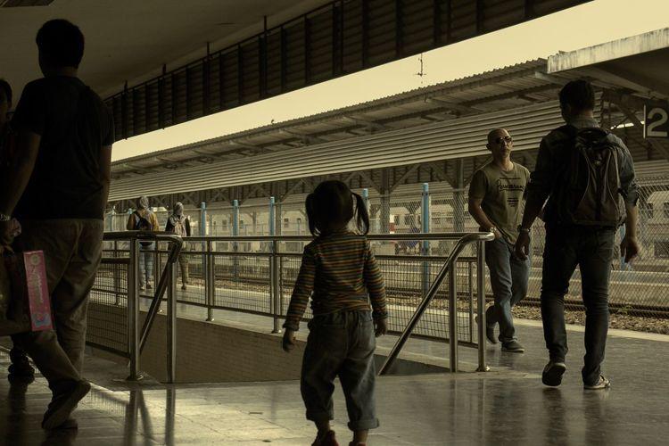 Rear view of people walking on zebra crossing