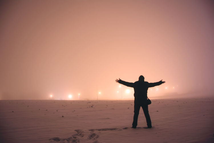Rear View Of Man With Arms Outstretched Standing On Snow Covered Field At Night