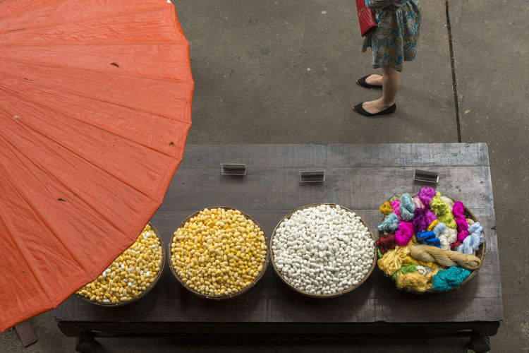 Low section of woman standing by silkworm cocoons on market stall