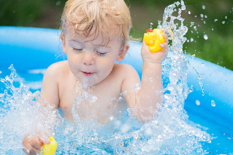 Cute boy splashing in wading pool