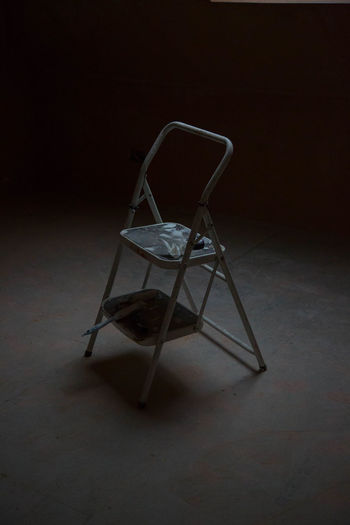 Empty chair on floor in abandoned building
