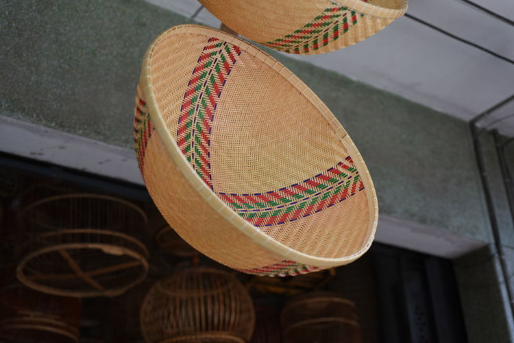 Low angle view of wicker basket hanging for sale on in store