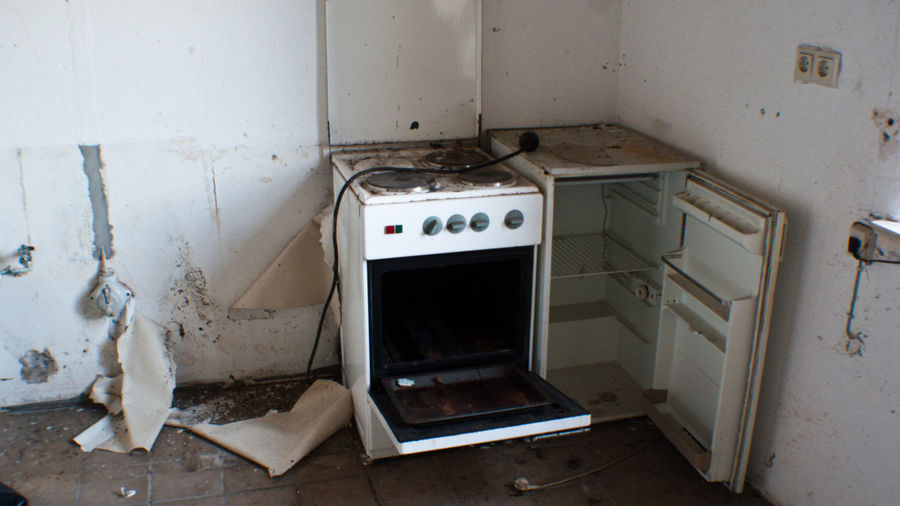 High angle view of abandoned stove and refrigerator in kitchen at home