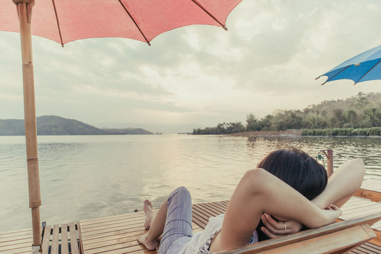 Rear view of woman relaxing on lake