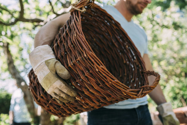 Close-up of man holding wicker basket on tree