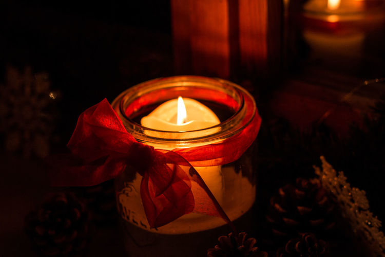 Burning candle in a glass and fir cones in the dark Candle Burning Illuminated Flame Fire Glowing Heat - Temperature Fire - Natural Phenomenon Indoors  Close-up Dark Lighting Equipment Tea Light Nature No People Decoration Red Spirituality Container Rose - Flower Electric Lamp