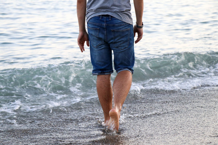 Walking On The Beach Man Water Sea One Person Casual Clothing Motion Beach Low Section Land Human Leg Human Body Part Leisure Activity Body Part Real People Shorts Lifestyles Standing Day Holiday Men Jeans Outdoors Ankle Deep In Water Wave Walking Vacations