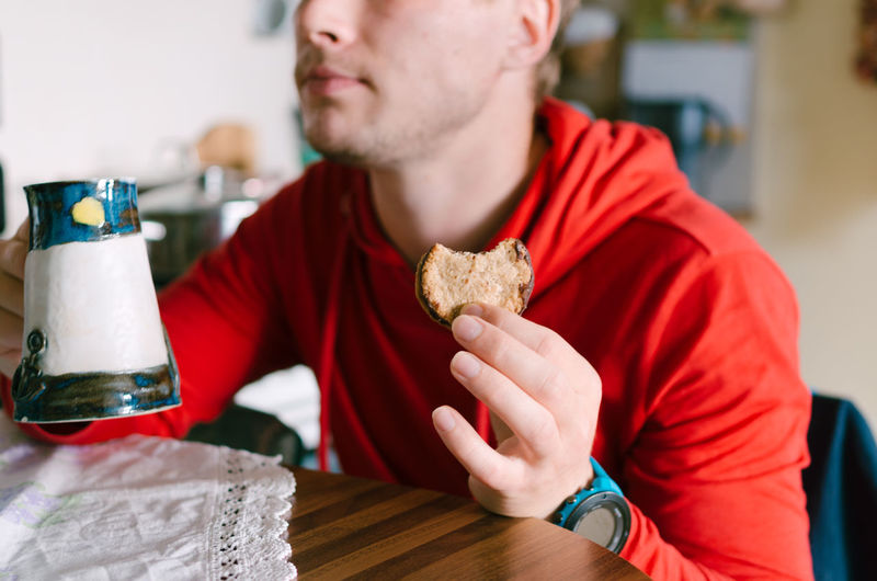 Midsection of man eating cookie at home