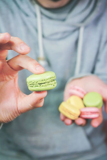 Food Food And Drink Holding Healthy Eating Fruit One Person Freshness Wellbeing Midsection Focus On Foreground Human Hand Front View Hand Real People Human Body Part Casual Clothing Lifestyles Close-up Day Temptation Finger Ripe Macaroon Macarons Dessert