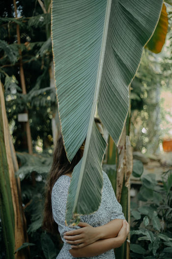 A young woman standing behind a plant leaf