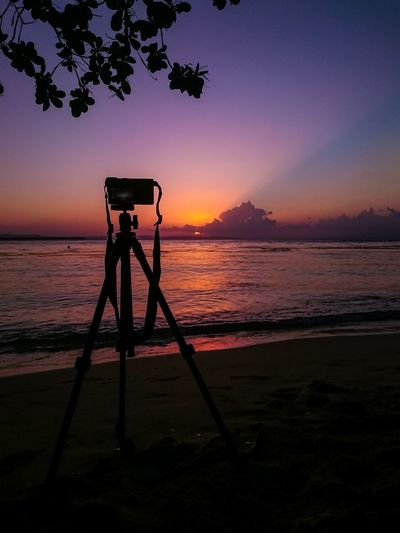 Silhouette camera on beach against sky during sunset