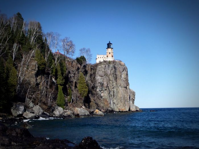 Split rock lighthouse on cliff by lake superior against sky