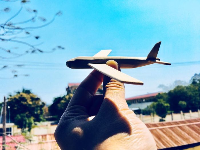 Close-up of person holding toy plane against sky