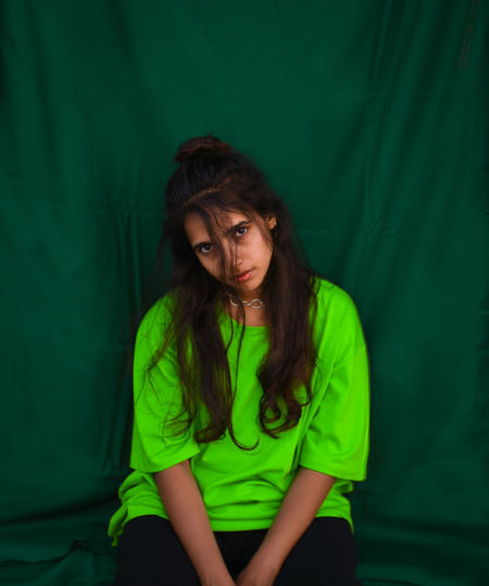 Portrait of young woman with long hair sitting against green fabric