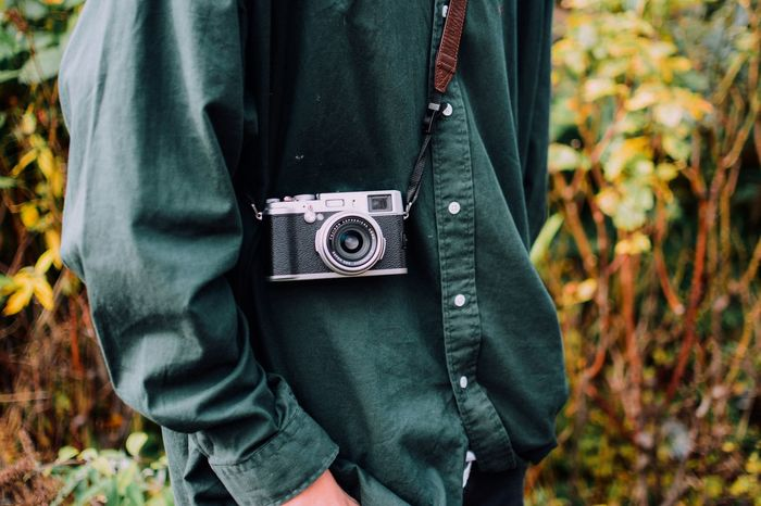 MIDSECTION OF MAN PHOTOGRAPHING WITH AUTUMN LEAVES
