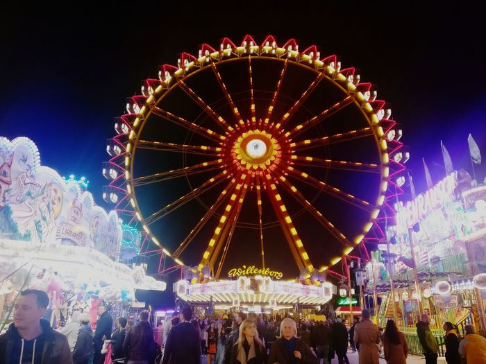 People in amusement park against sky at night
