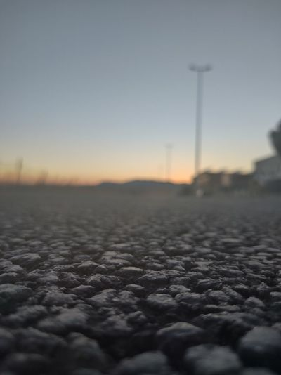 Surface level of snowy field against sky during sunset