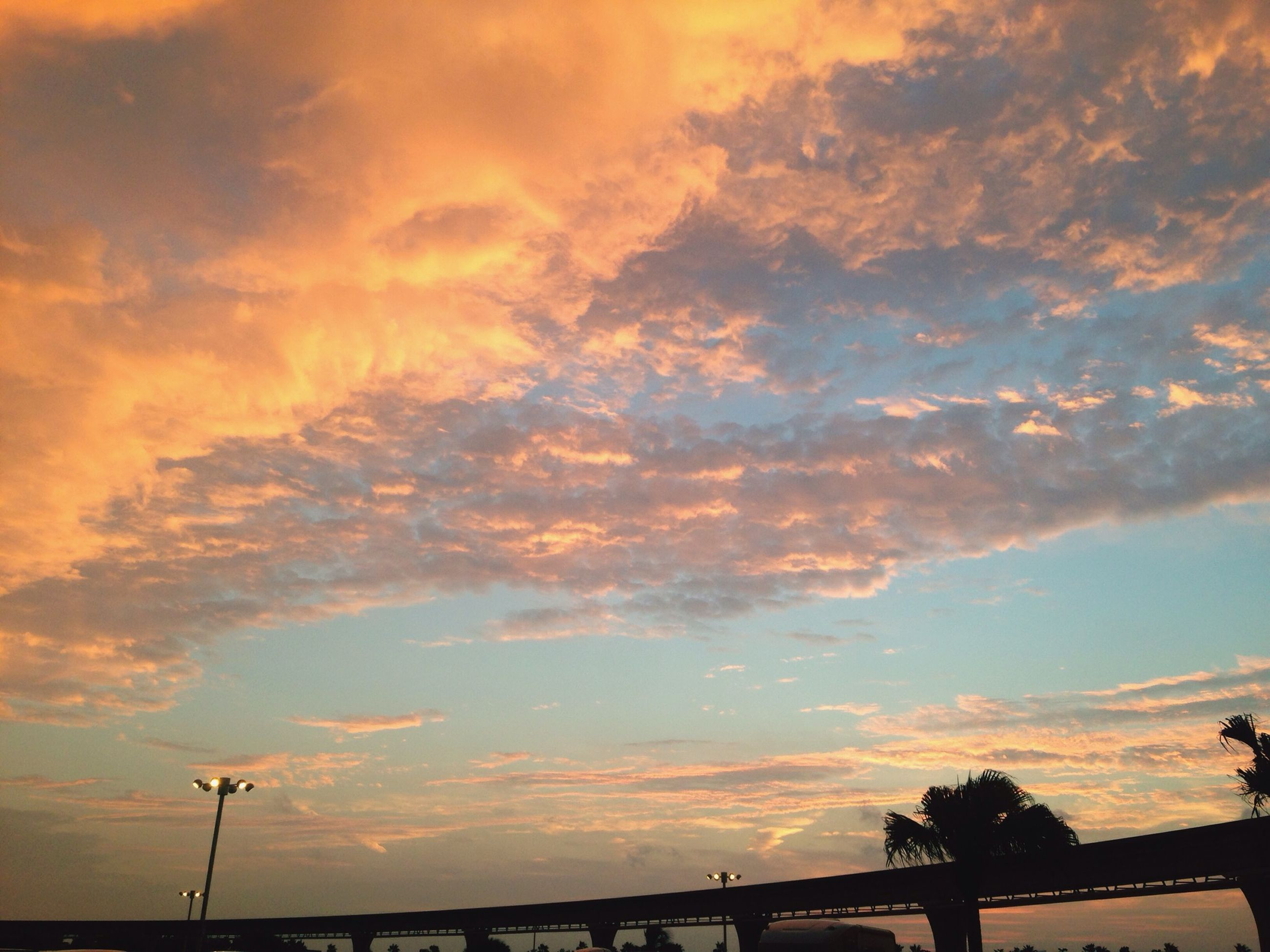 sunset, sky, silhouette, cloud - sky, low angle view, cloudy, beauty in nature, street light, orange color, scenics, tranquility, cloud, nature, dramatic sky, tranquil scene, idyllic, outdoors, no people, weather, dusk