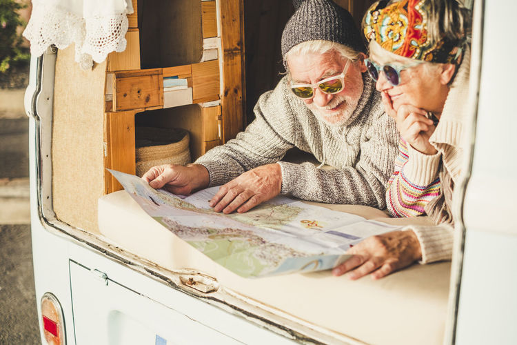 Old senior couple enjoy the travel vacation planning lay down inside a vintage van - happy lifestyle for retired people enjoying life - together forever couple - people traveling in summer Elderly Couple Traveler Vanlife Retirement Enjoying Life Hippie Cold Temperature Caucasian Casual Clothing Grandparents Mother Father Scarf Emotion Positive Vibes 65-69 Years Sunglasses Togetherness Friends Senior Adult Senior Women Sitting People Adult Lifestyles Indoors  Table Paper Glasses Activity Home Interior Real People Women Eyeglasses  Holding Leisure Activity Grandchild Tourist Two People Relationship Gray Hair White Hair Choice Alternative Lifestyle Map Lying Down Camping