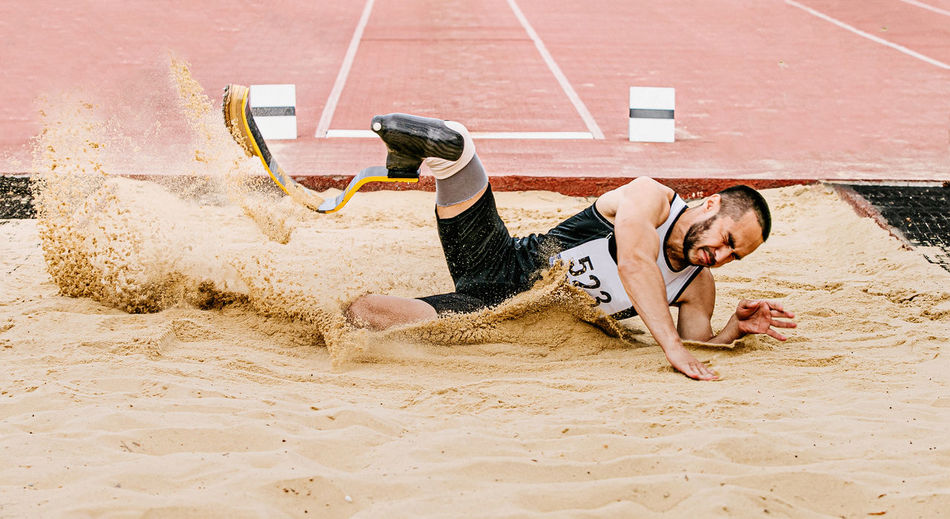 Male athlete falling on dirt