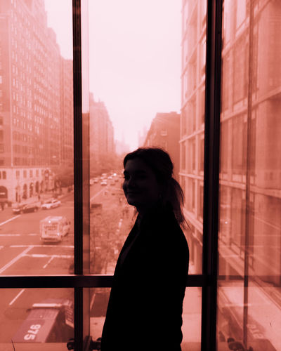 Woman standing by window against sky in city