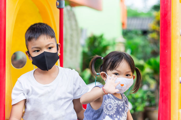 Portrait of siblings wearing masks playing in playground