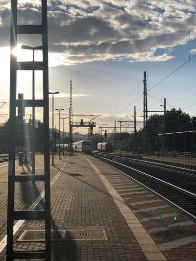 Railroad station against sky during sunset