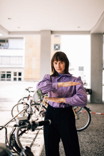 Portrait of smiling woman standing on bicycle