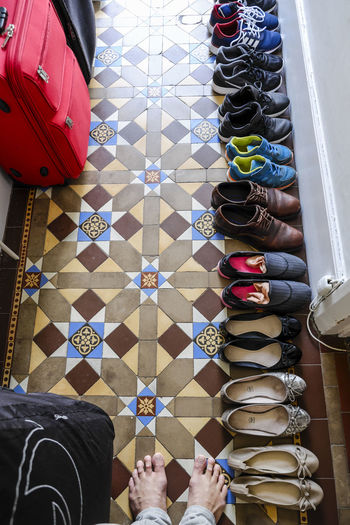 Row of shoes on the floor of door entrance. In A Row Bags Day Door Entrance Floor High Angle View Home Interior Human Leg Indoors  Lifestyles Multi Colored Shoes Top View One Step Forward