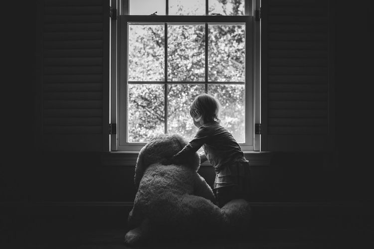 Girl with teddy bear by window at home