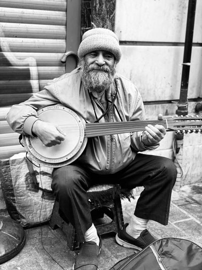 Man playing string instrument while sitting on footpath
