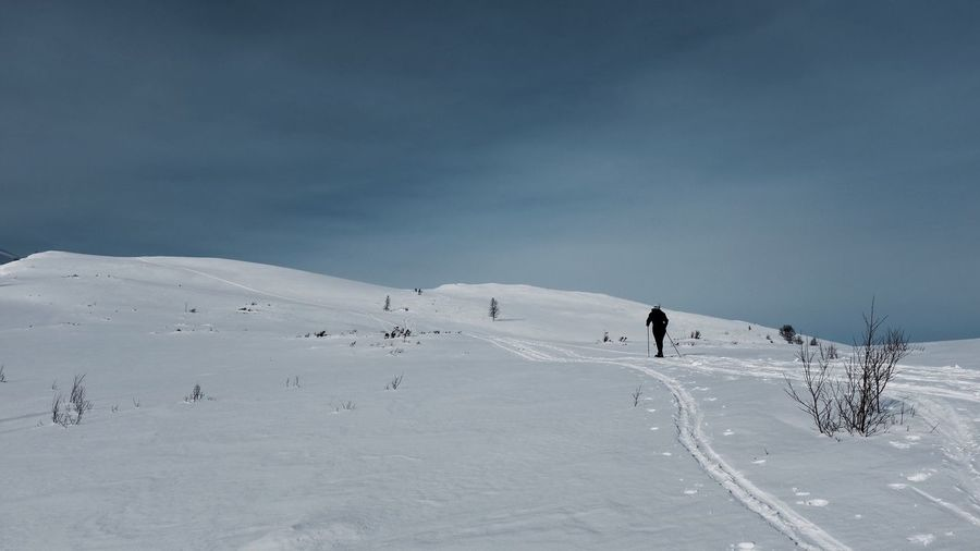 Rear View Of Person Hiking On Snow Landscape Against Sky