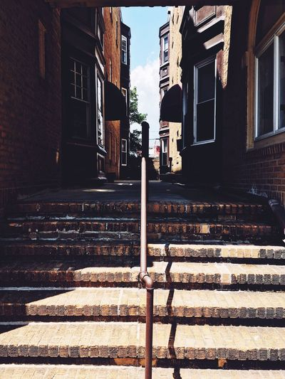 Steps amidst buildings in city on sunny day