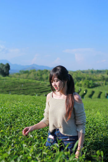 Contemplating woman picking leaves in tea plantation field against sky