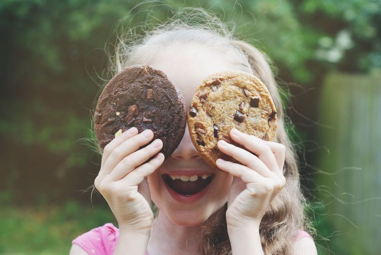 Close-Up Of Cut Girl Holding Cookies While Standing Outdoors