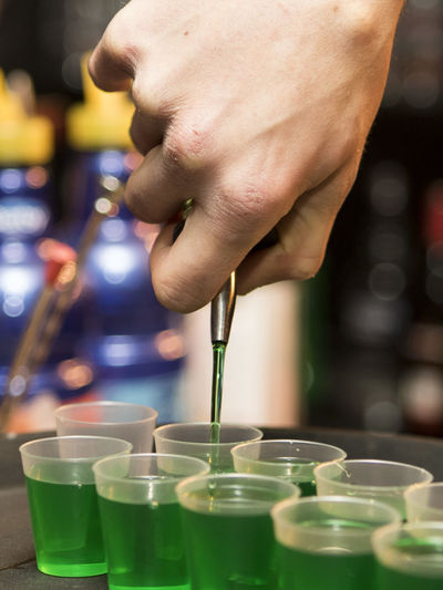 Cropped image of bartender pouring drink in shot glass at bar counter