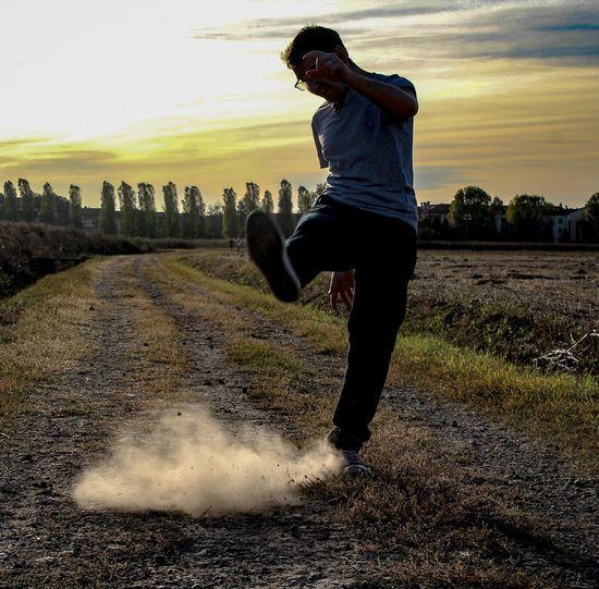 Full length of man running on field against sky during sunset