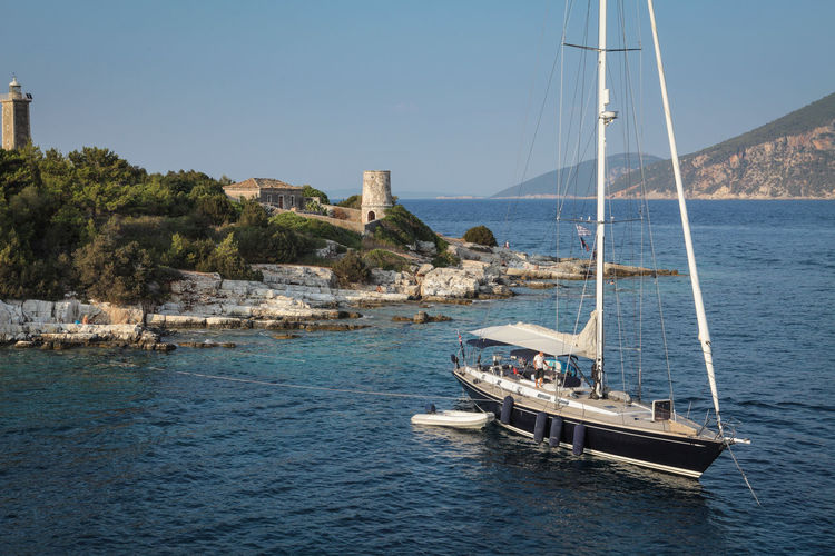Venetian lighthouse near Fiskardo village with moored yacht in front Lighthouse Rocky Shore Bay Luxury Yachting Yacht Outdoors Clear Sky Moored Beauty In Nature Travel No People Sailing Mast Sky Waterfront Sailboat Sea Transportation Nautical Vessel Adventure Summer Leisure Rich