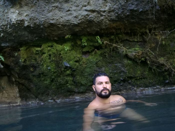 Portrait of young man swimming in pond against rock formation