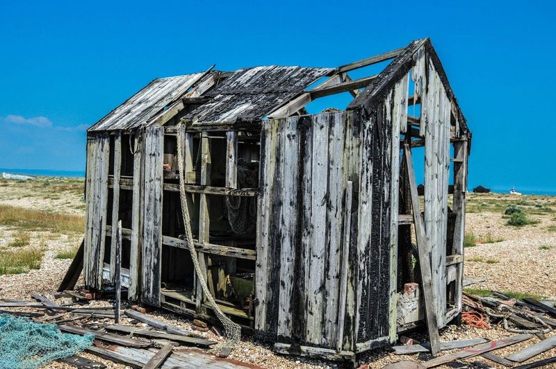 Old Damaged Wooden House On Field Against Blue Sky During Sunny Day