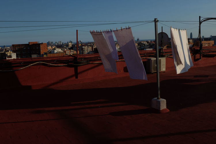 Clothes drying on clothesline against buildings in city