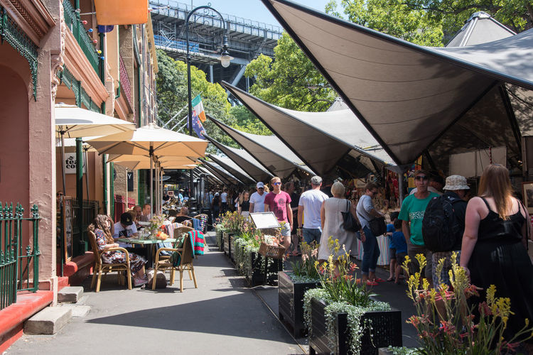Sydney,NSW,Australia-November 20,2016: Tourists at The Rocks open-air market in Sydney, Australia. Australia Lunch Shopping Tables And Chairs The Rocks The Tea Cosy Tourist Weekend Alfresco Blankets Cafe Consumerism Crowd Crowded Dining Market Stall Marketplace Real People Restaurant Retail  Retail Display Sails Sidewalk Cafe Sydney Umbrella