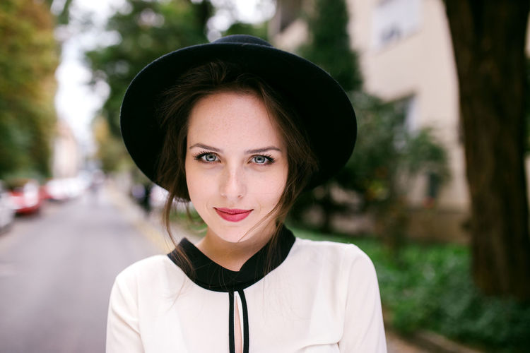 Portrait of young woman wearing hat standing outdoors